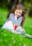 Mała dziewczynka z czerwonym jabłczanym obsiadaniem na trawie Obrazy Stock