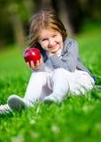 Mała dziewczynka z czerwonym jabłczanym obsiadaniem na zielonej trawie Fotografia Royalty Free