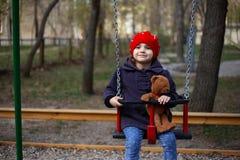 Mała dziewczynka z czerwonym kapeluszem na totter z jej misiem zdjęcia stock