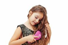 Mała dziewczynka z długie włosy czesaniem jej włosy obraz stock