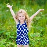 Mała dziewczynka z długim blond kędzierzawym włosy i podnosić rękami Obrazy Royalty Free