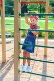 Mała dziewczynka z fryzura ogonem w cajgu kombinezonie wspina się w górę ściany obraz stock