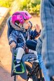 Mała dziewczynka z hełmem na kierowniczym obsiadaniu w rowerze obraz stock