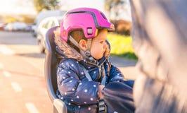 Mała dziewczynka z hełmem na kierowniczym obsiadaniu w rowerze fotografia stock