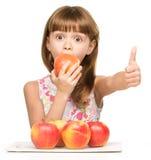 Mała dziewczynka z jabłkami pokazuje kciuk up podpisuje Zdjęcie Stock