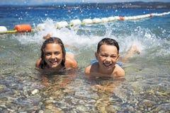 Mała dziewczynka z jej bratem na plaży Fotografia Royalty Free