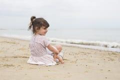 Mała dziewczynka z jej dolly na plaży zdjęcia royalty free