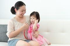 Mała dziewczynka z jej matką bawić się w lekarkach obrazy stock