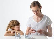 Mała dziewczynka z jej starym bratem tapetuje żurawie Obrazy Royalty Free