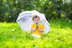 Mała dziewczynka z kolorowym parasolem bawić się w deszczu Zdjęcia Royalty Free