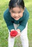 Mała dziewczynka z kwiat kapitałki mienia czerwieni różą w rękach Obraz Stock