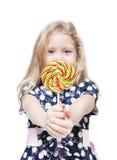 Mała dziewczynka z lizakiem odizolowywającym Ostrość na cukierku zdjęcia stock