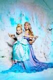 Mała dziewczynka z matką w princess sukni na tle w Zdjęcia Stock