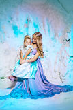 Mała dziewczynka z matką w princess sukni na tle w Zdjęcie Royalty Free