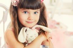 Mała dziewczynka z miękkiej części zabawki obsiadaniem na krześle. Zdjęcie Royalty Free