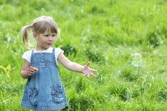 Mała dziewczynka z mydlanymi bąblami zdjęcie stock