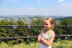 Mała dziewczynka z mydlanymi bąblami z miasta Zdjęcie Stock