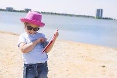 Mała dziewczynka z pastylka komputerem w rękach Słoneczny dzień na niebieskim niebie i plaży Dziewczyna w różowym kapeluszu i szk Zdjęcie Stock