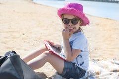 Mała dziewczynka z pastylka komputerem w rękach Słoneczny dzień na niebieskim niebie i plaży Dziewczyna w różowym kapeluszu i szk Zdjęcia Stock