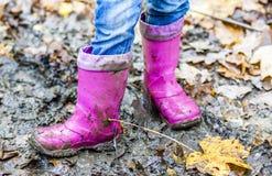Mała dziewczynka z różowymi wellys w kałuży fotografia stock