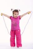 Mała dziewczynka z skok arkaną na bielu obraz stock