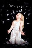 Mała dziewczynka z spada białymi piórkami Zdjęcia Royalty Free