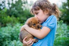 Mała dziewczynka z szczeniakiem w ona ręki Zdjęcie Royalty Free