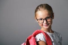 Mała dziewczynka z szkłami i plecakiem Obrazy Royalty Free