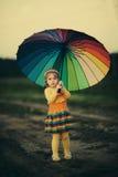 Mała dziewczynka z tęczy umrella w polu Fotografia Royalty Free