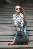 Mała dziewczynka z torbą w okularów przeciwsłonecznych pozować Zdjęcie Royalty Free