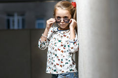 Mała dziewczynka z torbą w okularów przeciwsłonecznych pozować Zdjęcia Stock