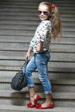 Mała dziewczynka z torbą w okularów przeciwsłonecznych pozować Fotografia Stock