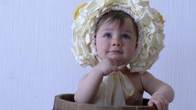 Mała dziewczynka z wiankiem na głowie śmia się na tło bielu ścianie zbiory