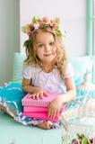 Mała dziewczynka zakrywająca z wiankiem i książkami Zdjęcie Stock