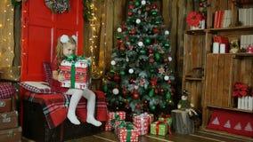 Mała dziewczynka znajdował nowego roku ` s prezent Jest szczęśliwa Zdjęcia Royalty Free