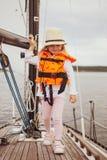 Mała Dziewczynka Zostaje na żaglówce w życie kamizelce, jachting, Chmurny niebo obraz royalty free