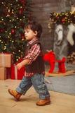 Mała elegancka chłopiec chodzi blisko choinki zdjęcie royalty free