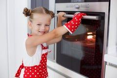 Mała gospodyni domowa angażował w wypiekowych muffins w kuchni w domu zdjęcia stock