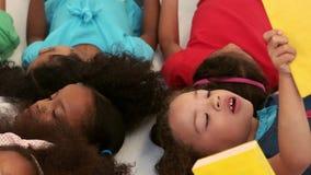 Mała grupa dzieciaków łgarski puszek i czytelnicze książki zbiory wideo