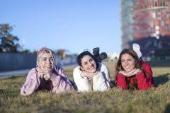 Mała grupa piękne dziewczyny śmia się wpólnie kłamać na trawie outdoors w parku obraz royalty free