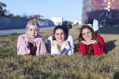 Mała grupa piękne dziewczyny śmia się wpólnie kłamać na trawie outdoors w parku zdjęcie stock
