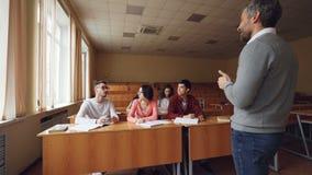 Mała grupa ucznie opowiada nauczyciel, młody człowiek podnosi rękę i pytać pytanie, uśmiechnięty pedagog jest zdjęcie wideo