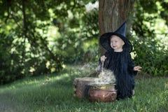 Mała Halloween czarownica outdoors z kotłem Obraz Stock
