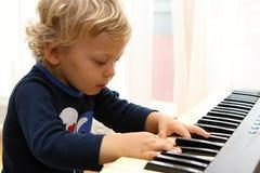 Mała kędzierzawa chłopiec bawić się fortepianową klawiaturę Obrazy Stock