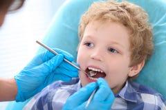 Mała kędzierzawa chłopiec otwiera jego usta szerokiego podczas inspekci oralny zagłębienie dentystą obraz stock