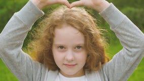 Mała kędzierzawa dziewczyna w parku pokazuje serce zbiory