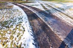 Mała kałuża na drodze, odbicie w wodzie blisko łąki Śnieg i zima zdjęcia royalty free