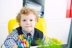Mała Kaukaska chłopiec patrzeje kamery obsiadanie przy komputerem w biurze Obrazy Stock