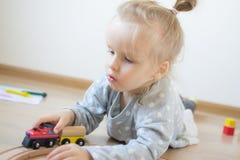 Mała Kaukaska dziewczyna Bawić się z Drewnianymi kolei edukacji Wczesnymi grami w domu zdjęcie stock
