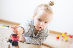Mała Kaukaska dziewczyna Bawić się z Drewnianymi kolei edukacji Wczesnymi grami w domu fotografia stock